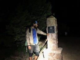 A hiker stands next to the northern terminus of the Arizona Trail at night.