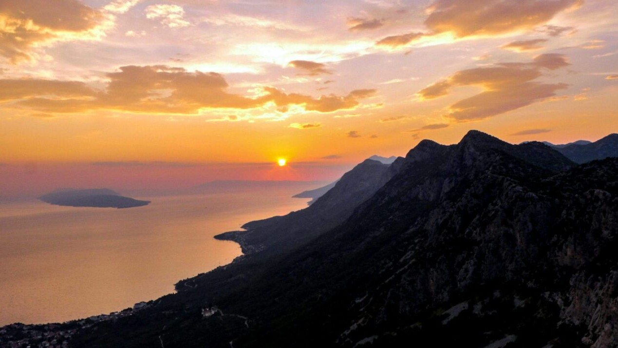 The sun sets over a mountain range and a large body of water on the Croatian Long Distance Trail.