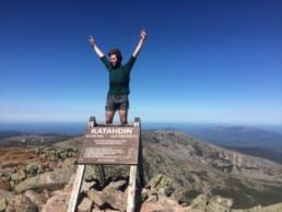 A man stands on the Mt Katahdin trail sign.