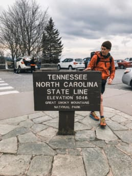 A hiker standing next to the Tennessee and North Carolina State Line sign on the Appalachian Trail.