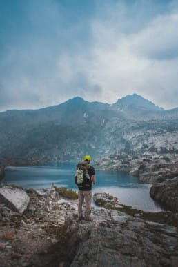 A hiker looking out at a lake.