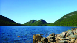 A blue lake with rocky shores sits in front of green rounded mountains and a blue sky.