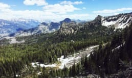A view from the ridge shows an evergreen forest, distant mountains, and lingering snow.