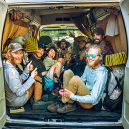 A group of hikers sitting in a van.