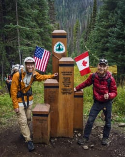Two hikers standing next to the northern terminus of the Pacific Crest Trail.