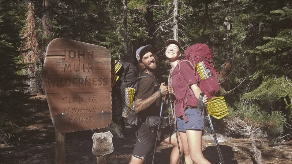 Two hikers pose in front of a John Muir Wilderness sign.