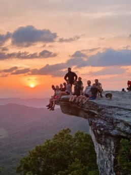 A group of hiker sit on a rock looking at the sunrise.