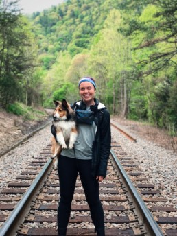 A girl holding her dog on the train tracks on the Appalachian Trail.