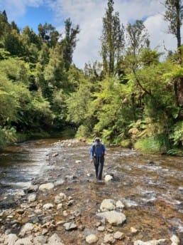 A man hiking in the water on the Te Araroa.