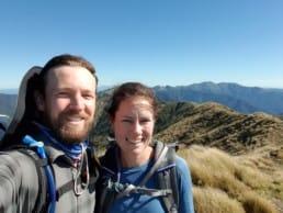A man and woman smiling while hiking the Te Araroa.