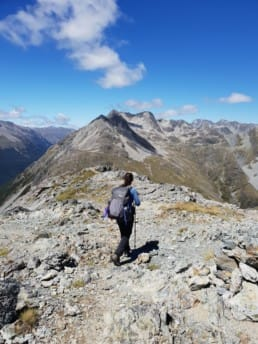 A hiker standing on the top of a mountain on the Te Araroa.
