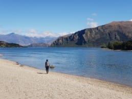A hiker standing next to a lake on the Te Araroa.