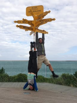 Two hikers posing next to the monument sign on the Te Araroa.