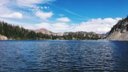 A sparkling blue lake sits in front of a rocky mountain ridge and evergreen forests.