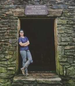 A hiker leaning up against the door of a shelter on the Appalachian Trail.