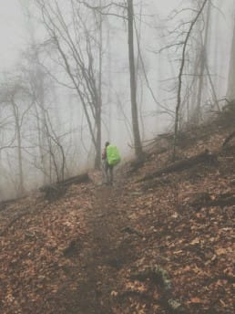A hiker standing in the foggy woods on the Appalachian Trail.