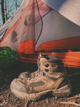 Hiking boots in front of a tent.