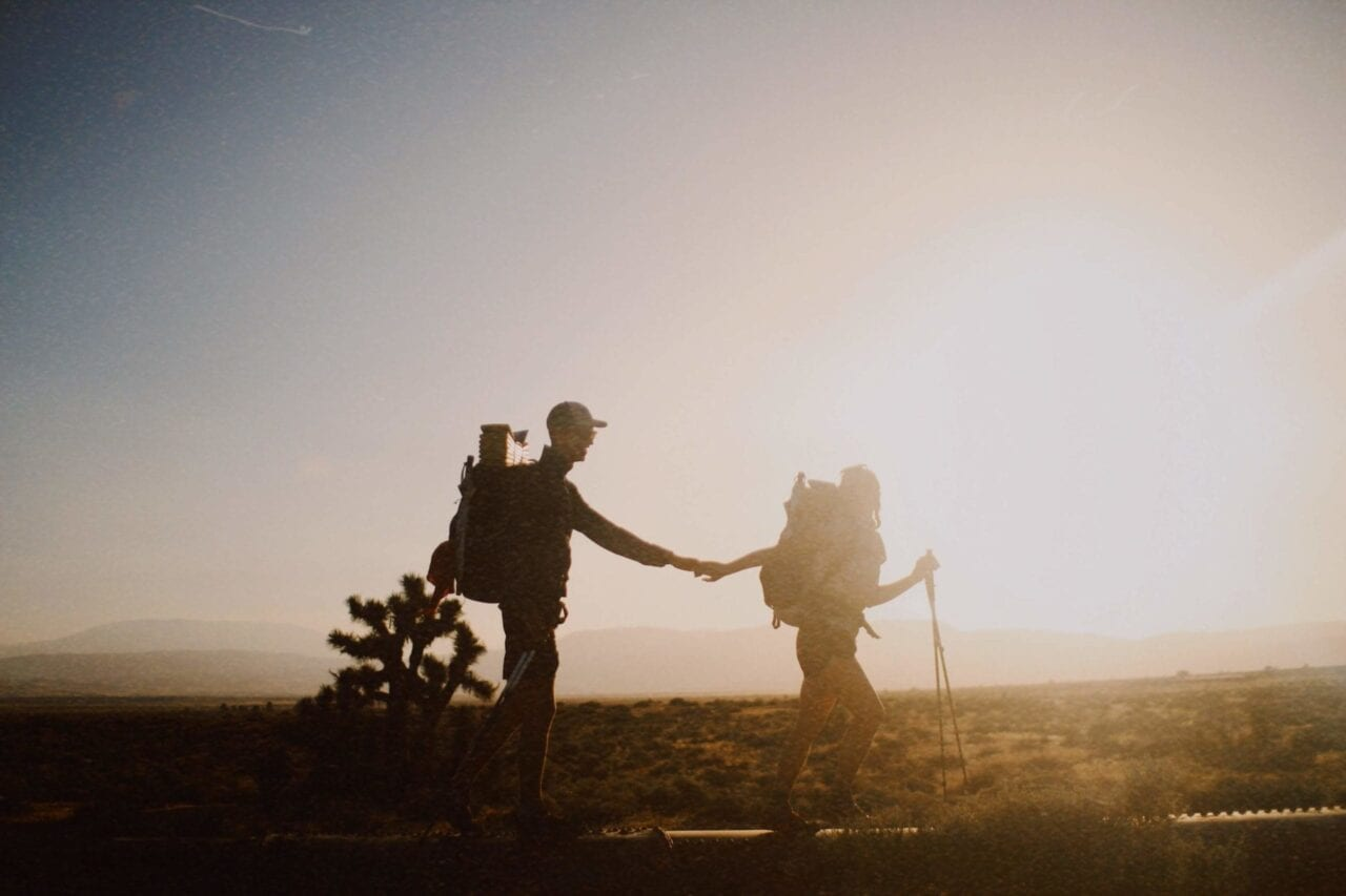 Two hikers holding hands are silhouetted against a sunset.