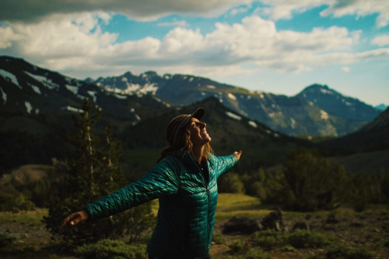 A hiker in a teal jacket spreads her arms and smiles against a backdrop of tall mountains.