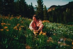A hiker wearing a pink shirt sits in a green field with wildflowers.