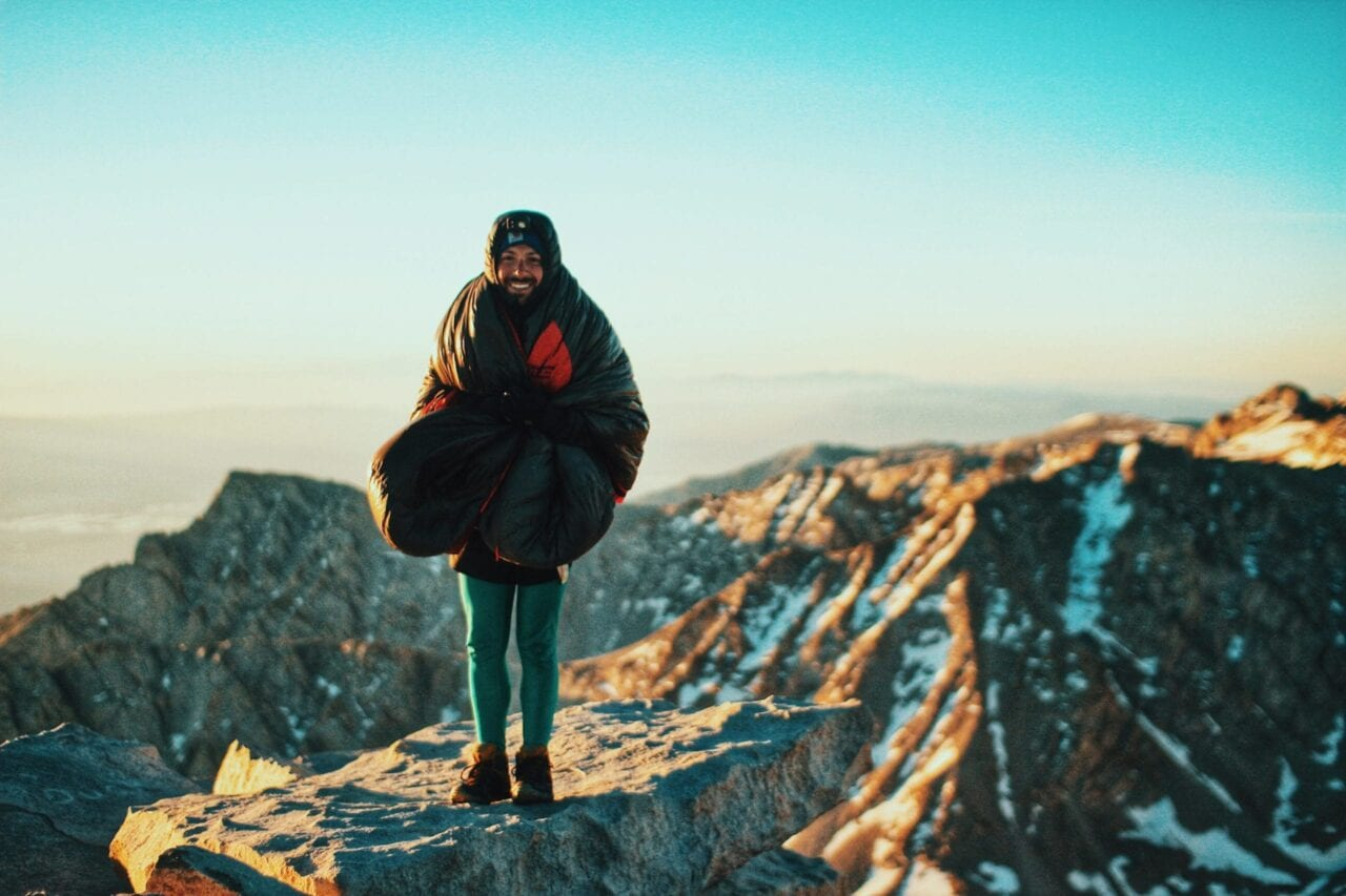 A hiker wrapped in a sleeping bag stands on a rocky outcropping with a sunrise and mountain peaks in the background.