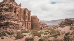 A hiker walks through a desert landscape near a historic structure.