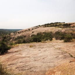 A large smooth rock outcropping has a few scrub trees on top.