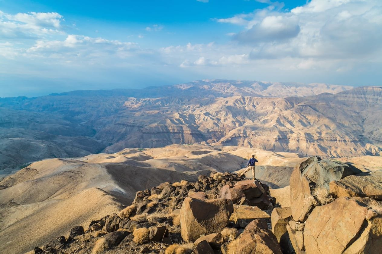 A hiker stands on top of tan rocks against a backdrop of mountains.