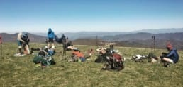 A group of hikers and their gear sit in a meadow.