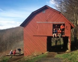 A group of hikers sit in the window of a red barn.