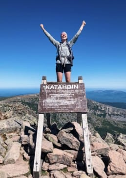 A hiker standing on top of the Mount Katahdin sign on the Appalachian Trail.
