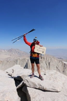 A hiker standing on the top of Mount Whitney.