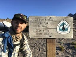 A hiker posing next to a Pacific Crest Trail sign.