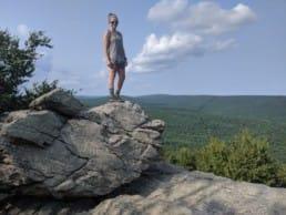 Thru-hiker on a rock ledge at the Appalachian Trail