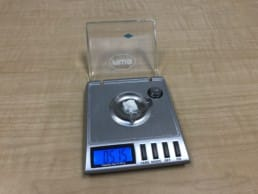 A scale with a little bit of toothpaste on it.