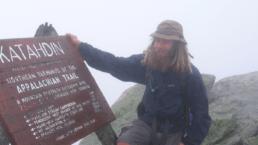 Guthook standing next to the Mount Katahdin sign.