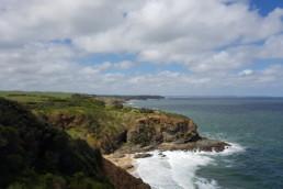 Ocean waves lap a sandy beach below rocky cliffs and green headlands.