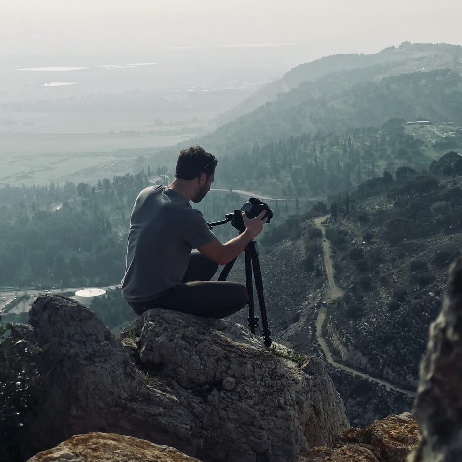 A hiker with a camera and a tripod takes a picture of distant mountains.