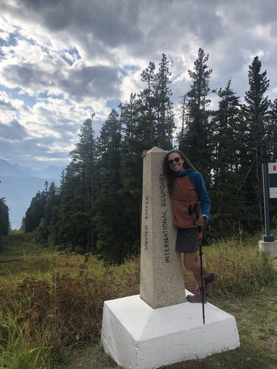 A woman standing on the CDT terminus.