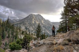 A hiker standing on a trail with a mountain in the background.