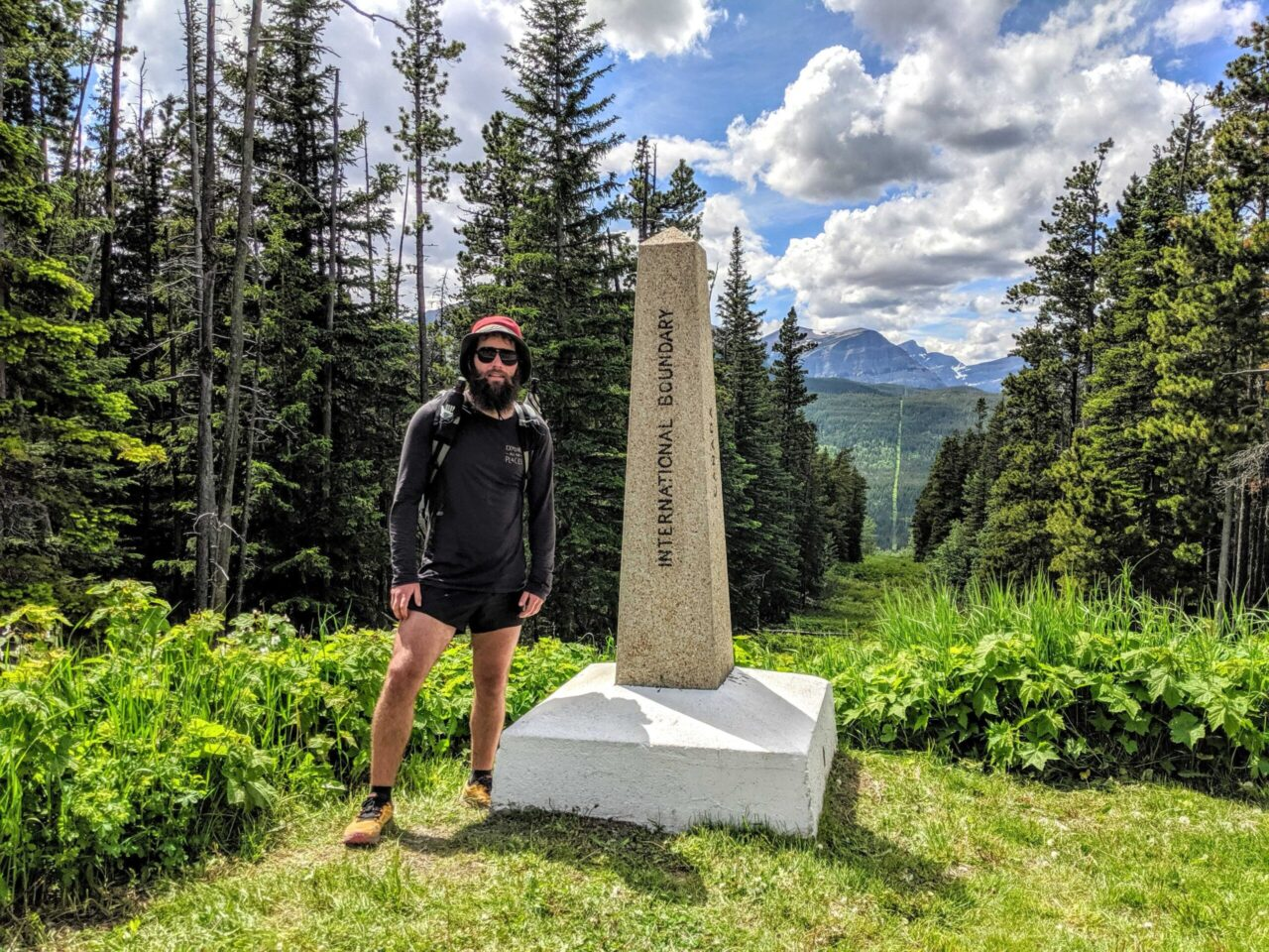 A thru-hiker standing next to the northern terminus of the Continental Divide Trail.