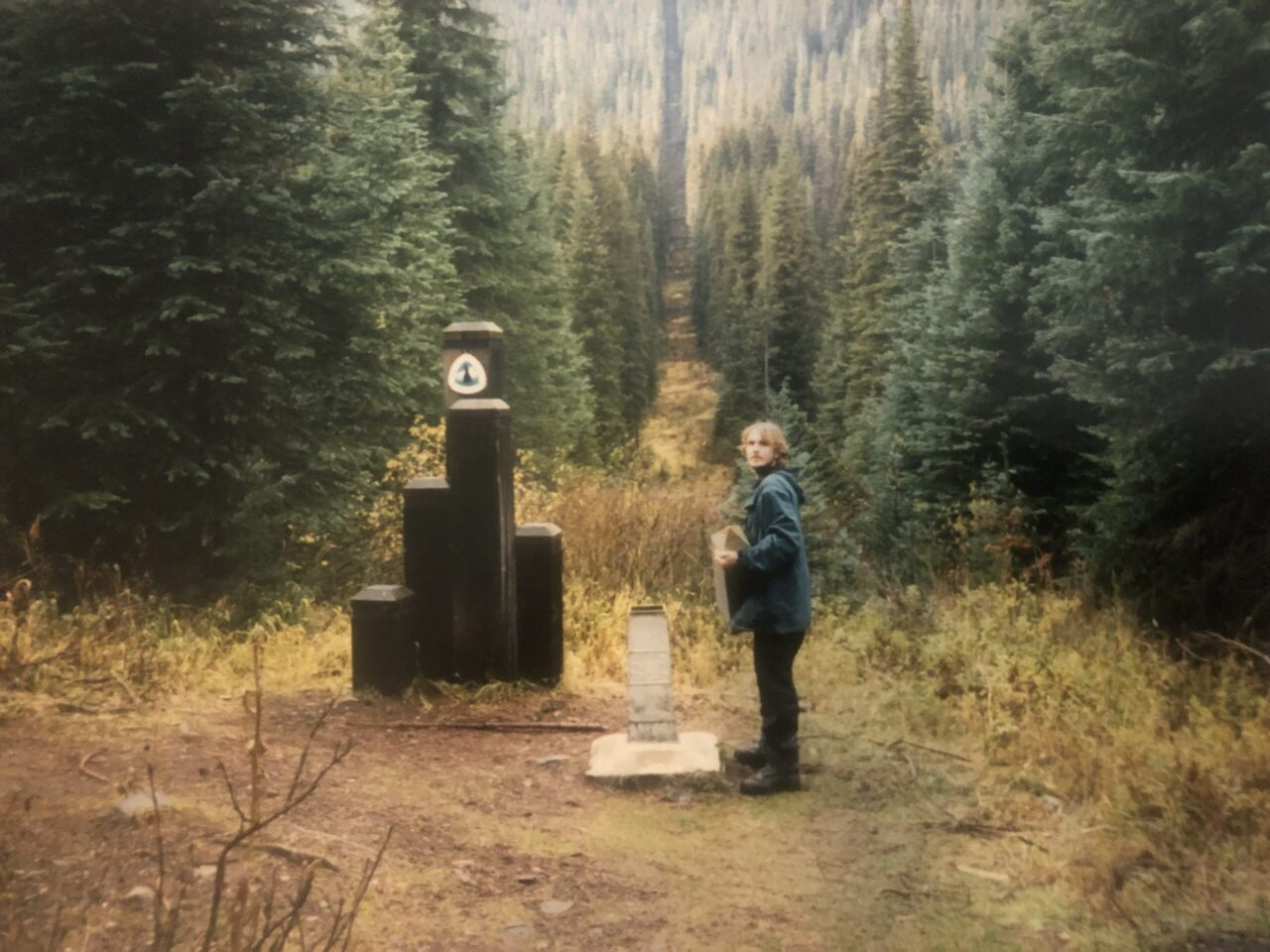 A hiker standing next to the PCT northern terminus in 1997.