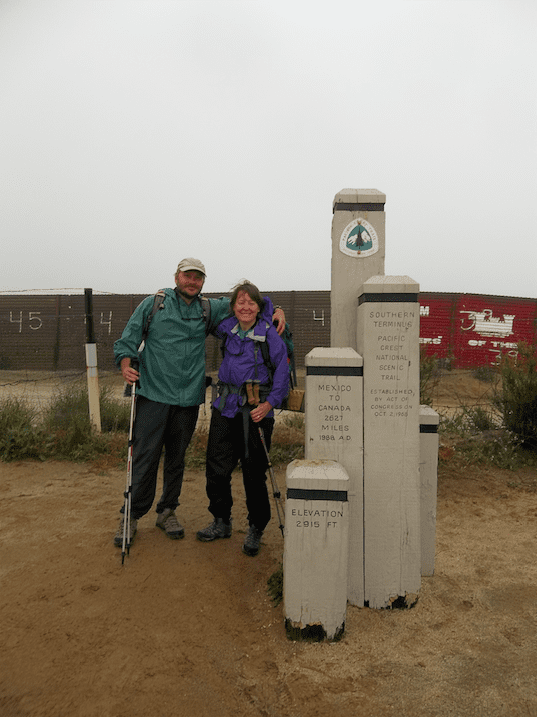 Two thru-hikers standing next to the southern terminus of the PCT.