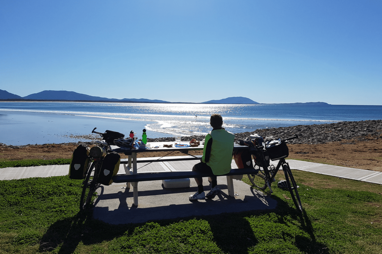 A person sitting at a picnic table next to a bike looking out at the ocean.