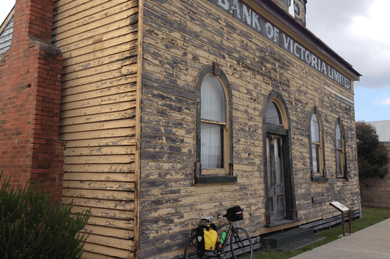 A bike propped up against an old building.
