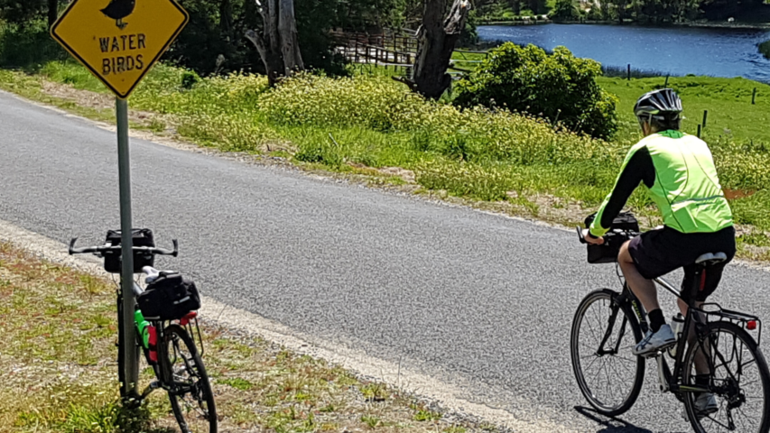 A person cycles along a paved path in Australia