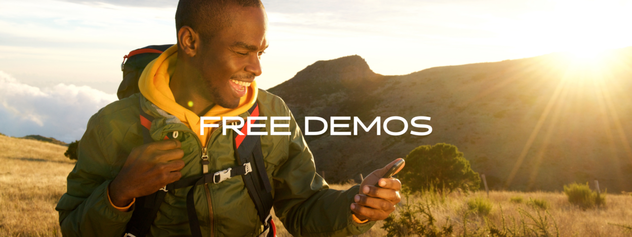 A man holding a phone with text that says Free Demos.