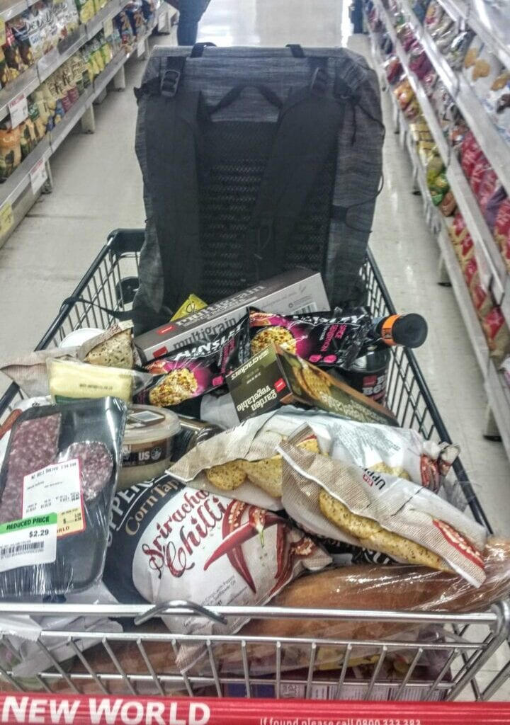 A shopping cart full of food and a backpack.
