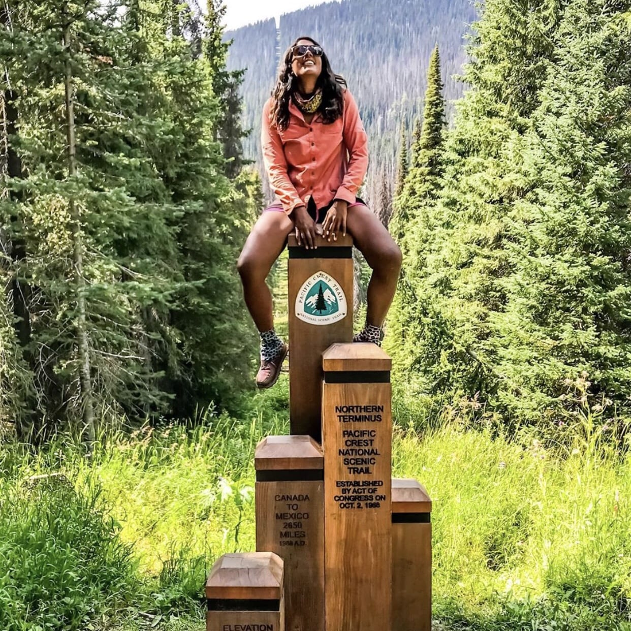 A woman sitting on to of the northern terminus on the PCT.