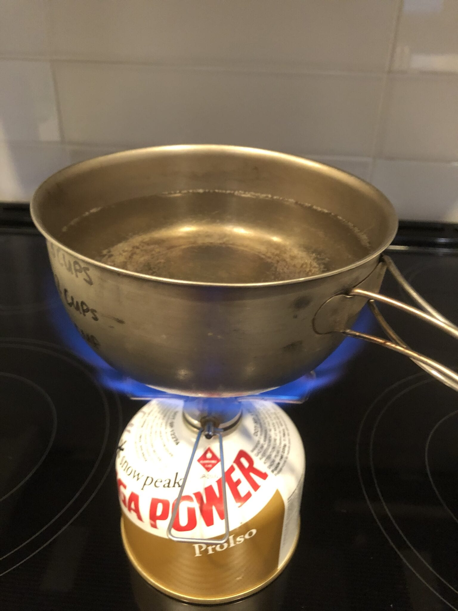 A backpacking stove boiling a pot of water.